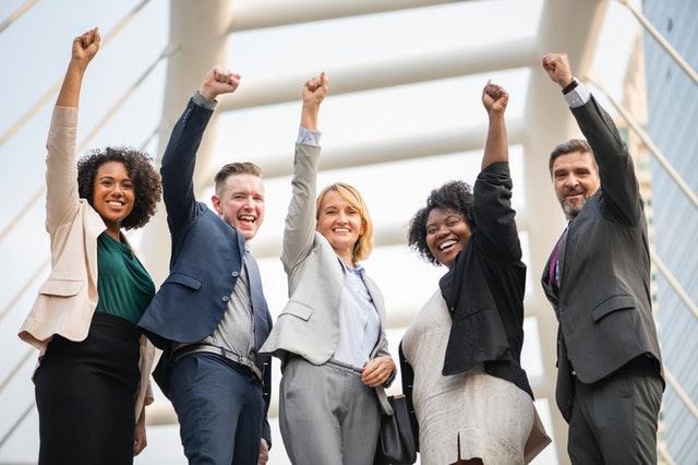 vítězné gesto skupiny mladých podnikatelů