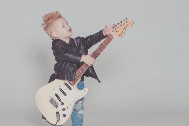 chlapeček hrající na elektrickou kytaru